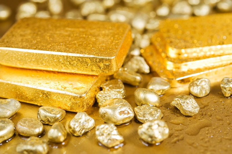 fine gold ingots and nuggets on a wet golden background ** Note: Shallow depth of field